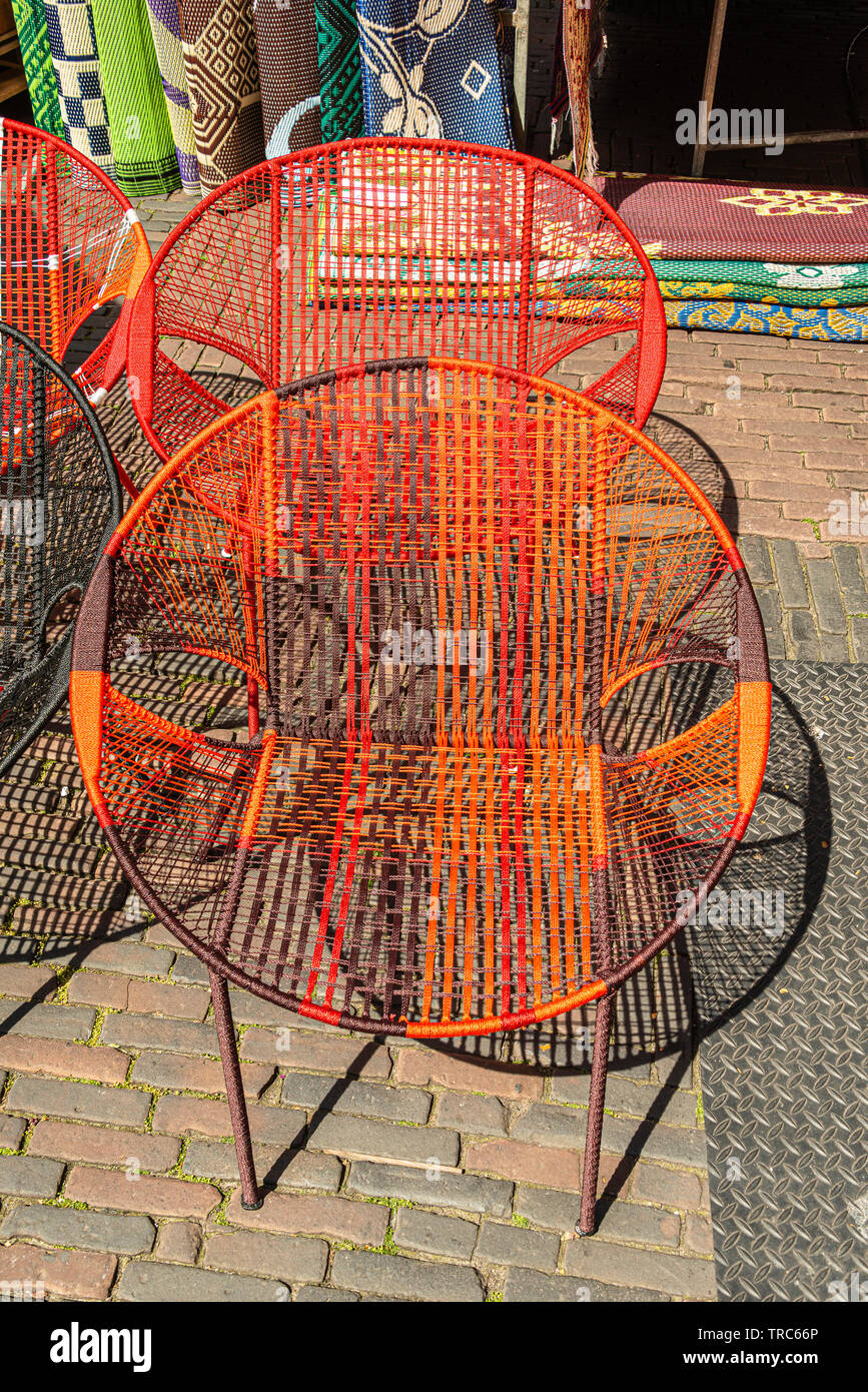 two orange tinted chairs with mesh structure for sale at the market - Stock Image
