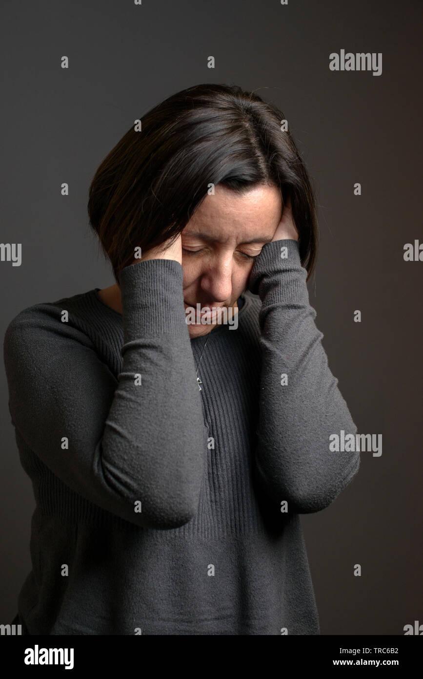 Woman suffers severe headache - Stock Image