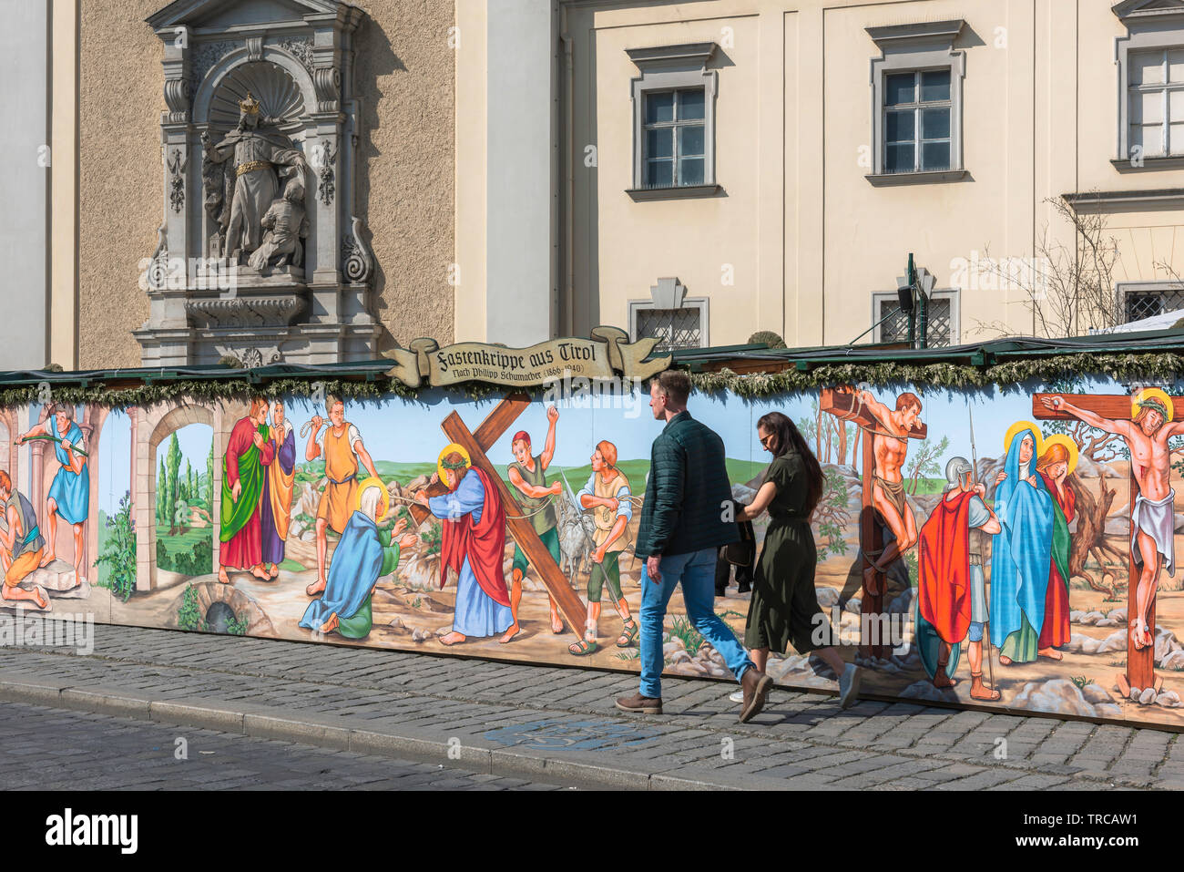 Vienna Easter, view of a young couple walking past a colorful illustration of The Passion Of Christ beside the Schottenkirche in the centre of Vienna. Stock Photo