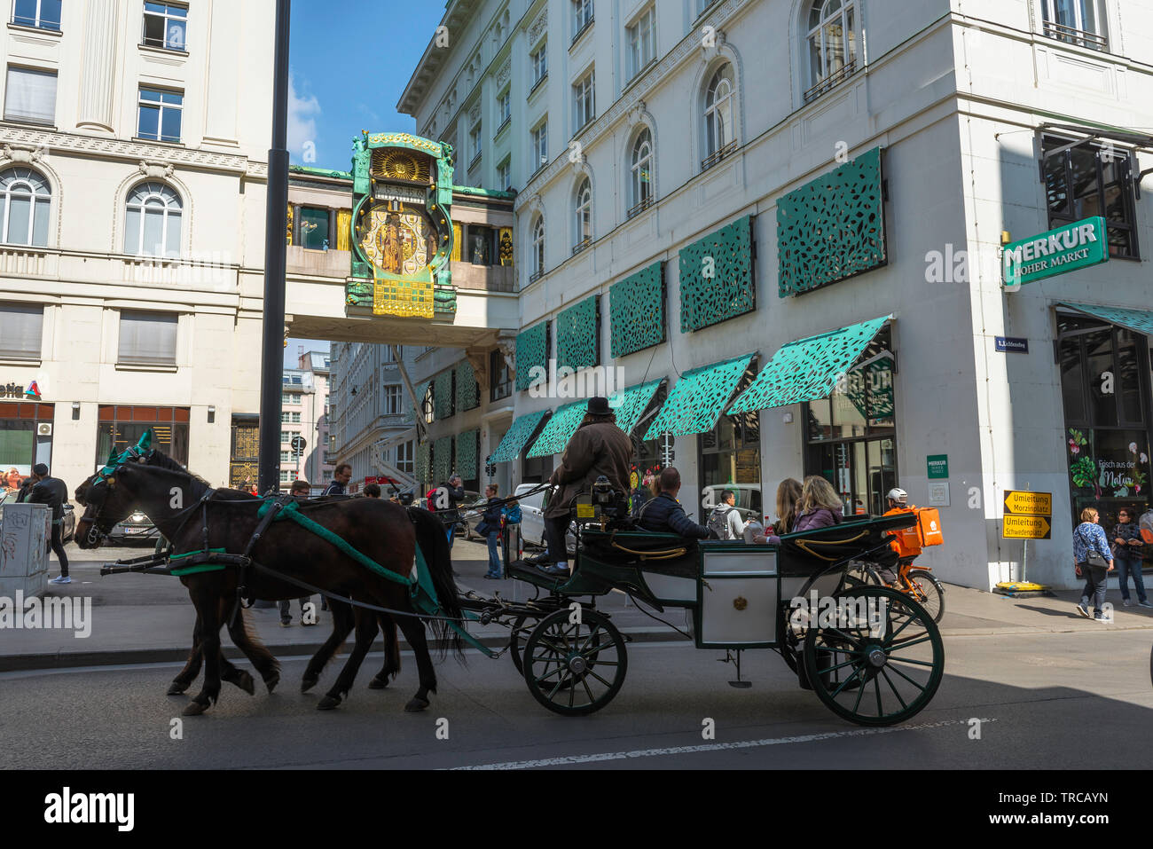 Vienna tourism, view of a horse drawn carriage containing tourists passing the Anker Clock in Hoher Markt in the Old Town area of Vienna, Austria. Stock Photo