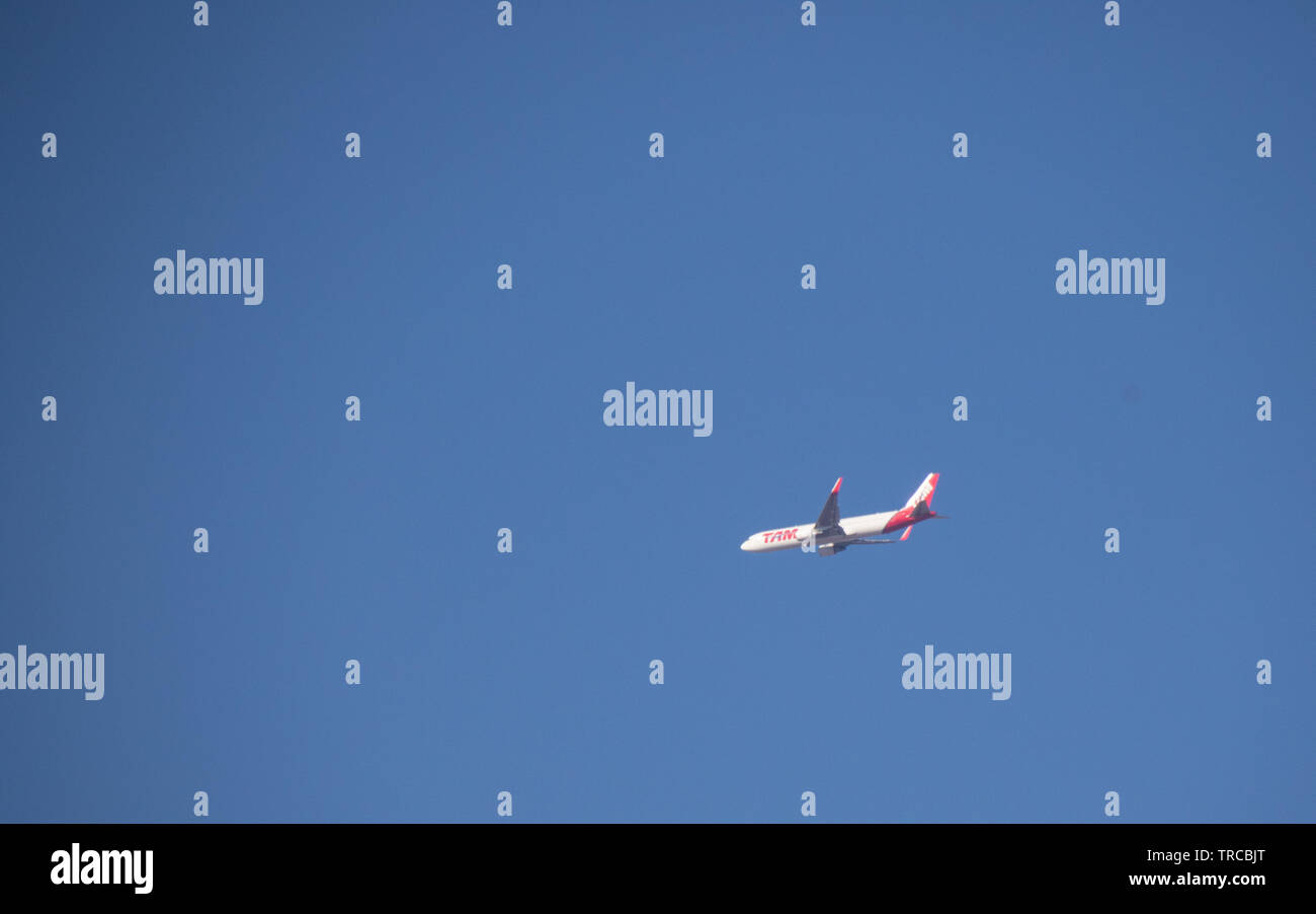 Johannesburg, South Africa - A TAM airliner on an international flight isolated in the sky above the city image with copy space in landscape format Stock Photo