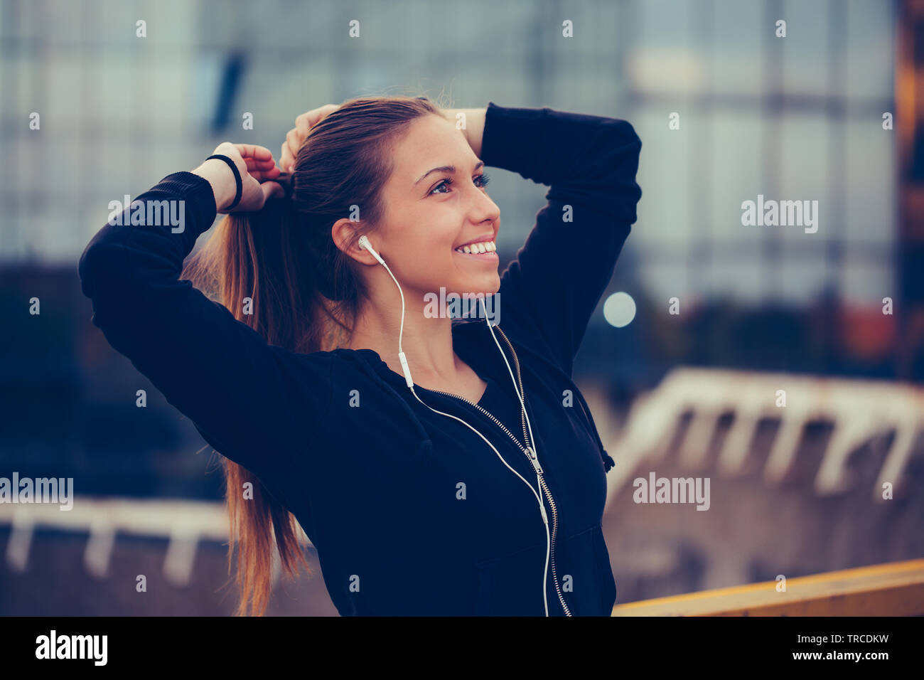 Beautiful sporty girl tying hair before her workout on the bridge. - Stock Image