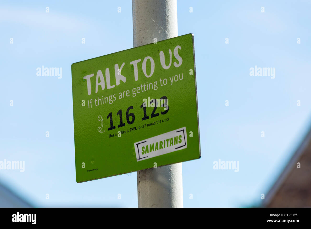 Talk to us if things are getting to you Samaritans sign on post at railway train station at Bournemouth, Dorset UK in June Stock Photo