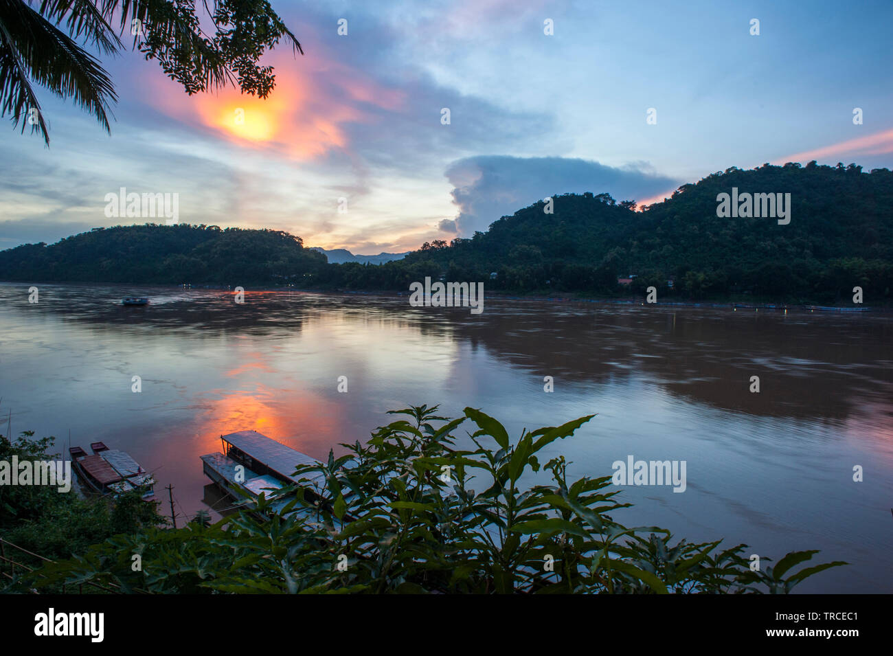 Sunset over the Mekong River from one of the tourist bars along the waterfront in Luang Prabang, Lao PDR (Laos). - Stock Image