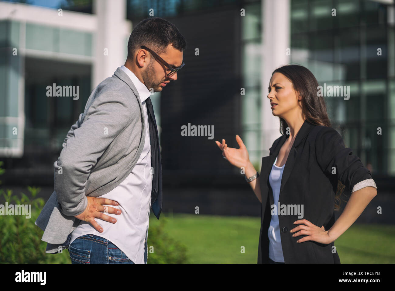 Overworked businessman is talking to colleague after work. - Stock Image