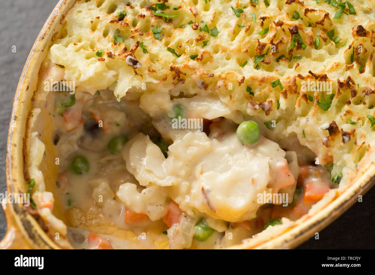 A homemade fish pie with ingredients including discounted kippers from a supermarket, a pollack fillet, cheap, frozen vegetables and discounted mashed - Stock Image