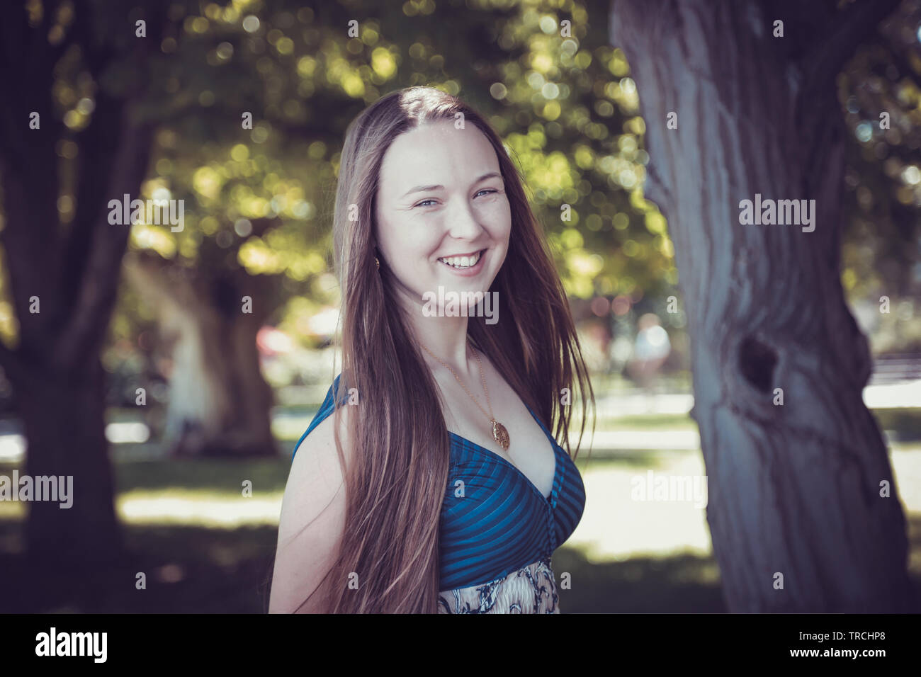 Caucasian woman happy running in summer / spring city park joyful and smiling in sundress around trees. Beautiful fresh multiracial caucasian. Caucasi - Stock Image