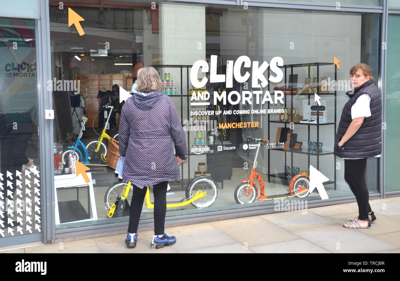 June 3rd, 2019.  Amazon and Enterprise Nation started a new initiative today to  help small businesses sell on the high street.  They plan to open ten 'Clicks and Mortar' shops in the uk as a one year pilot project.  The first shop opened today on St Mary's Gate in city centre Manchester. The shops aim to help selected online brands grow their high street presence. Passers-by look in the window of the new shop in Manchester, uk. - Stock Image
