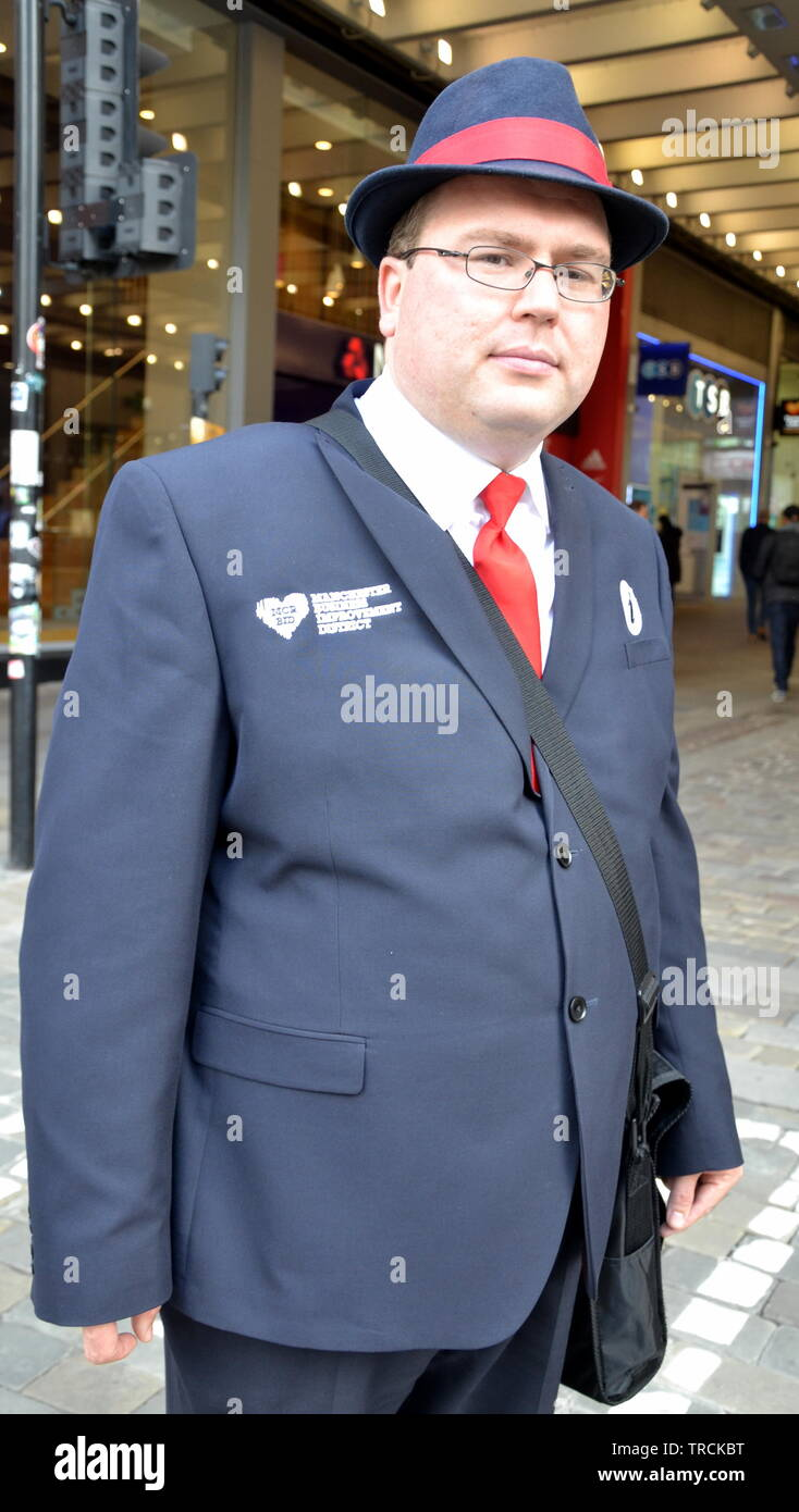 A male tourist information guide on Market Street, city centre Manchester, uk - Stock Image