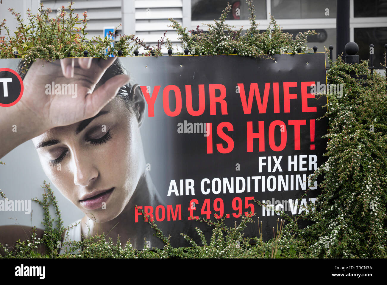 'Your wife is hot!' on advertizing hoarding for car air conditioning. UK - Stock Image