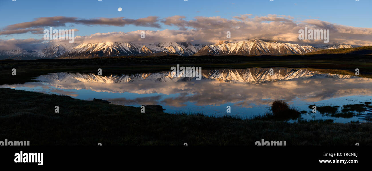Moonset over Laurel Mountain and Mt. Morrison during sunrise near the town of Mammoth Lakes, in the sierra mountains of California as seen from Long V - Stock Image