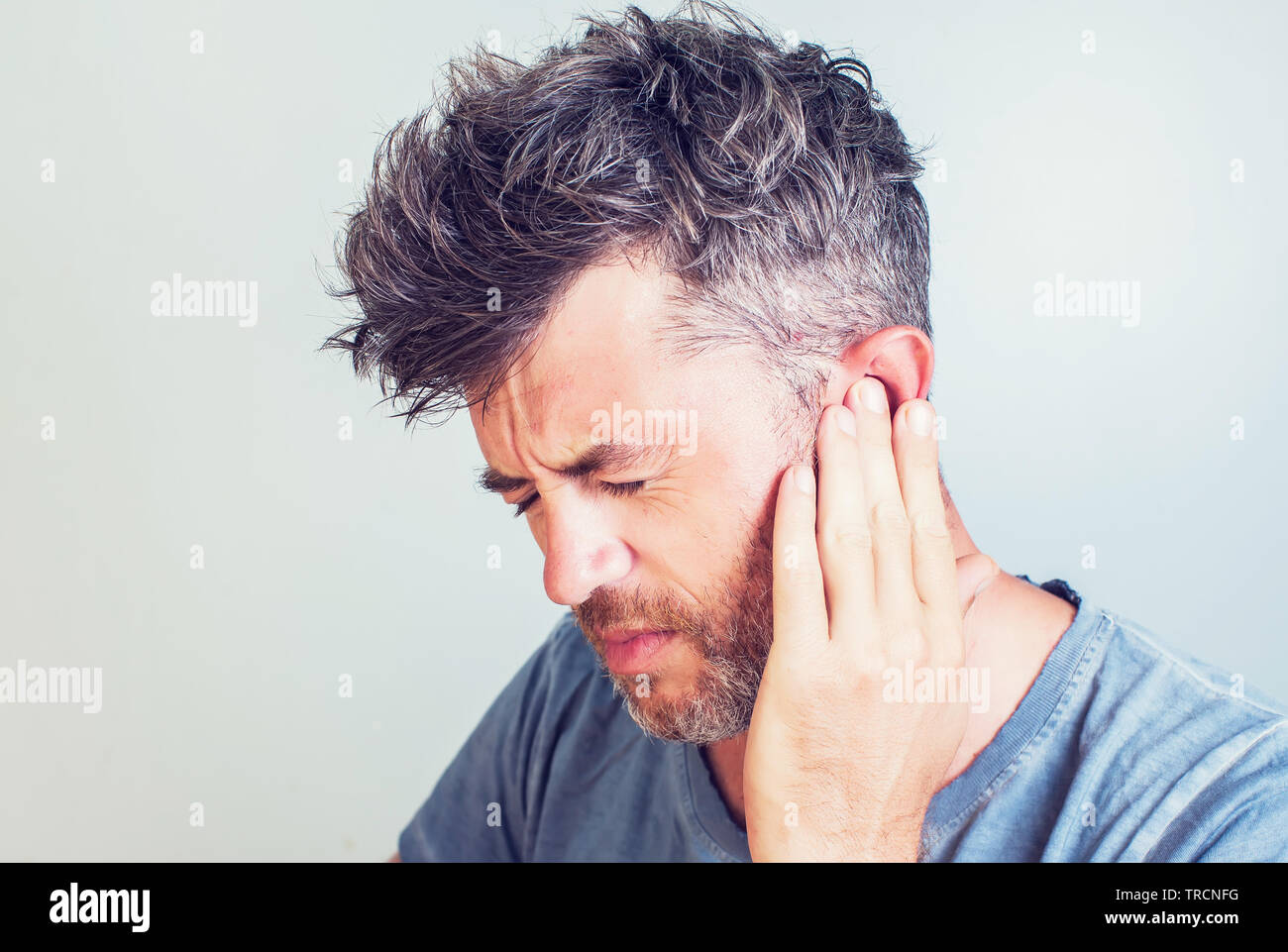 Man with earache is holding his aching ear body pain concept - Stock Image