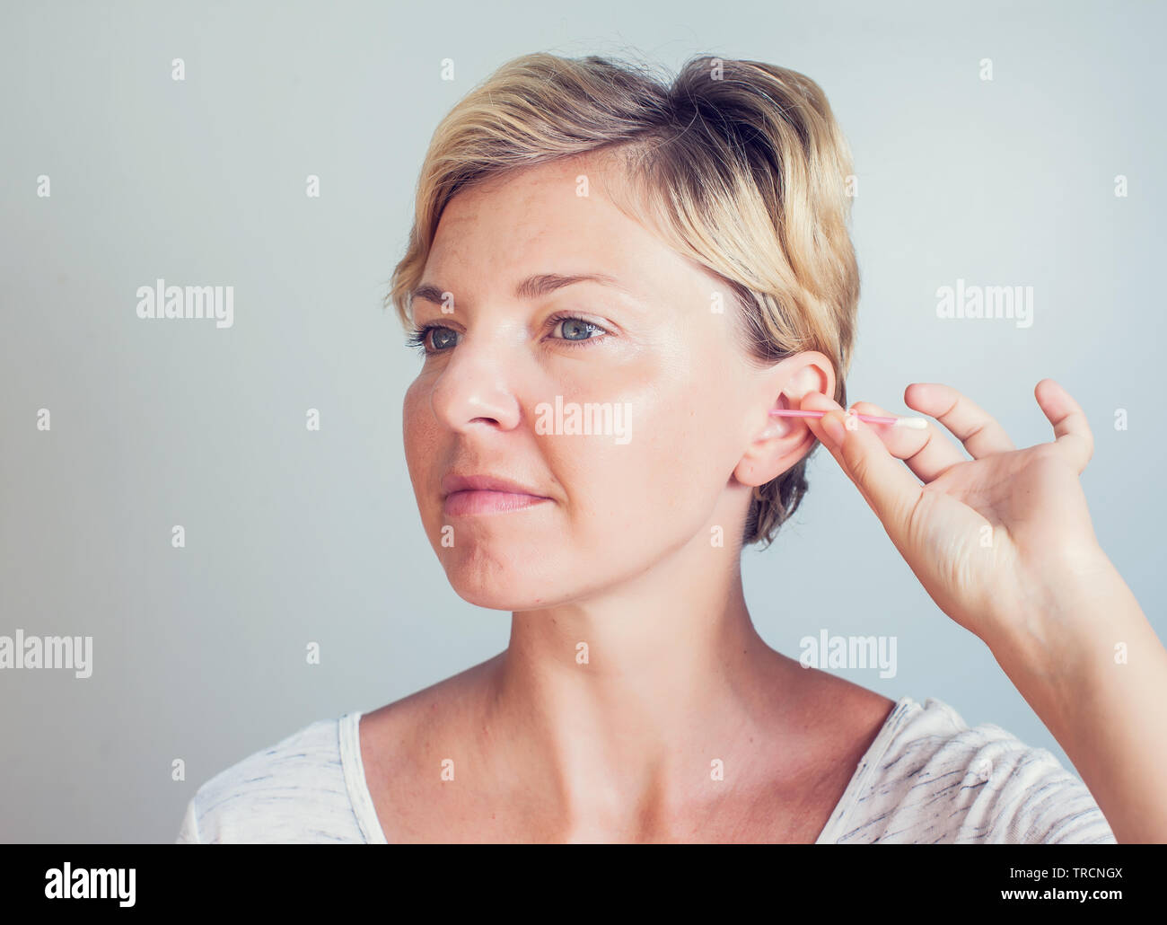 Woman cleans ears with cotton sticks isolated on white Stock Photo