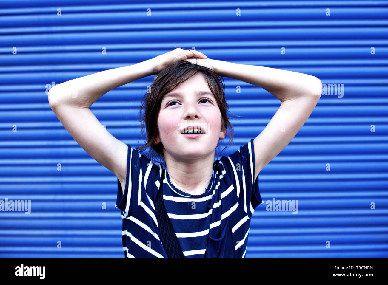Ten year old boy in stripy blue shirt - Stock Image