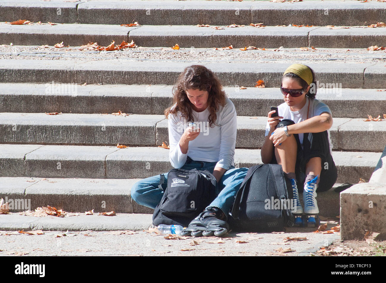 Two young women using mobile phones in The Retiro park. Madrid, Spain. - Stock Image