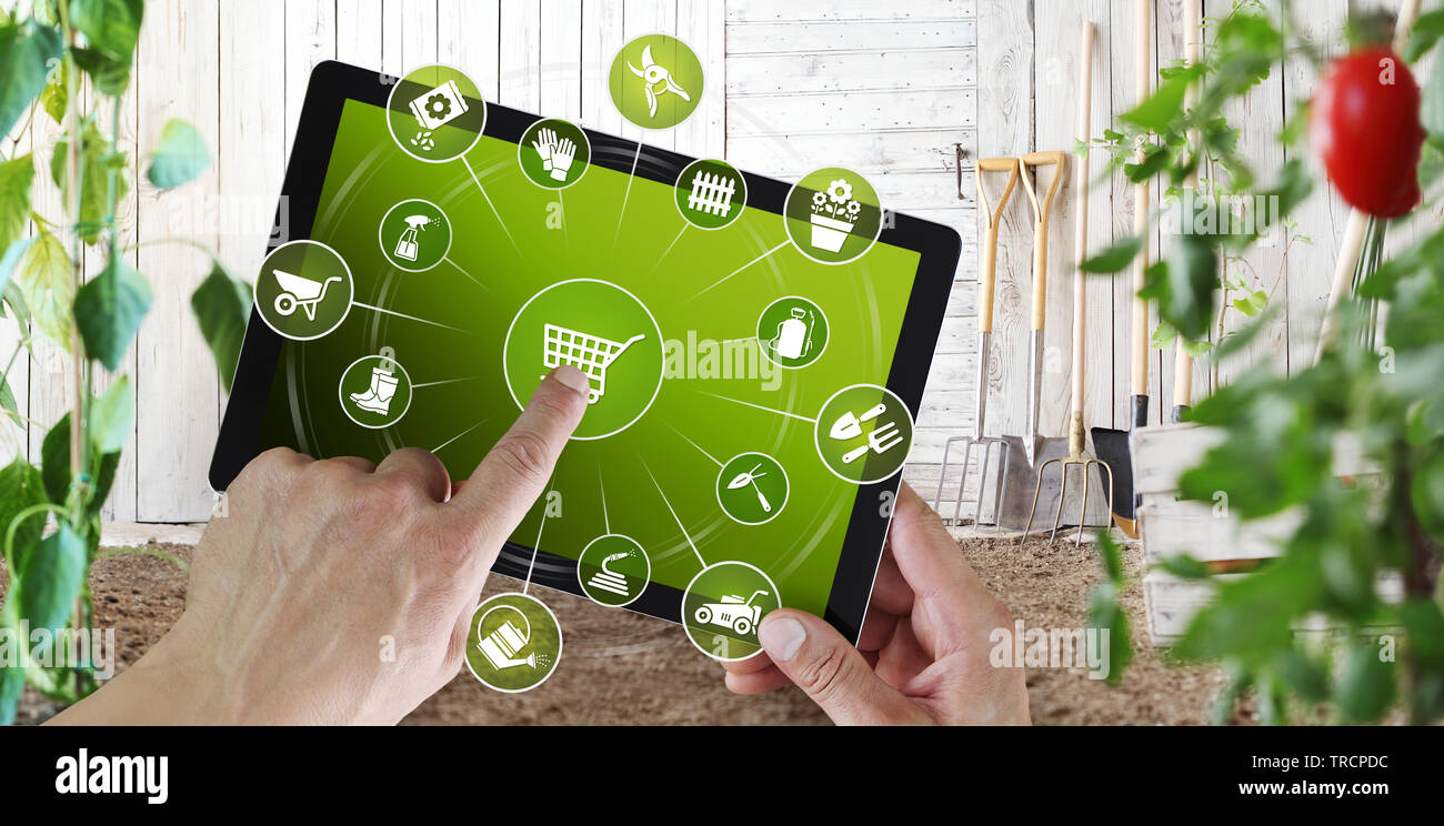 gardening equipment e-commerce concept, online shopping on digital tablet, hand pointing and touch screen with garden tools icons Stock Photo