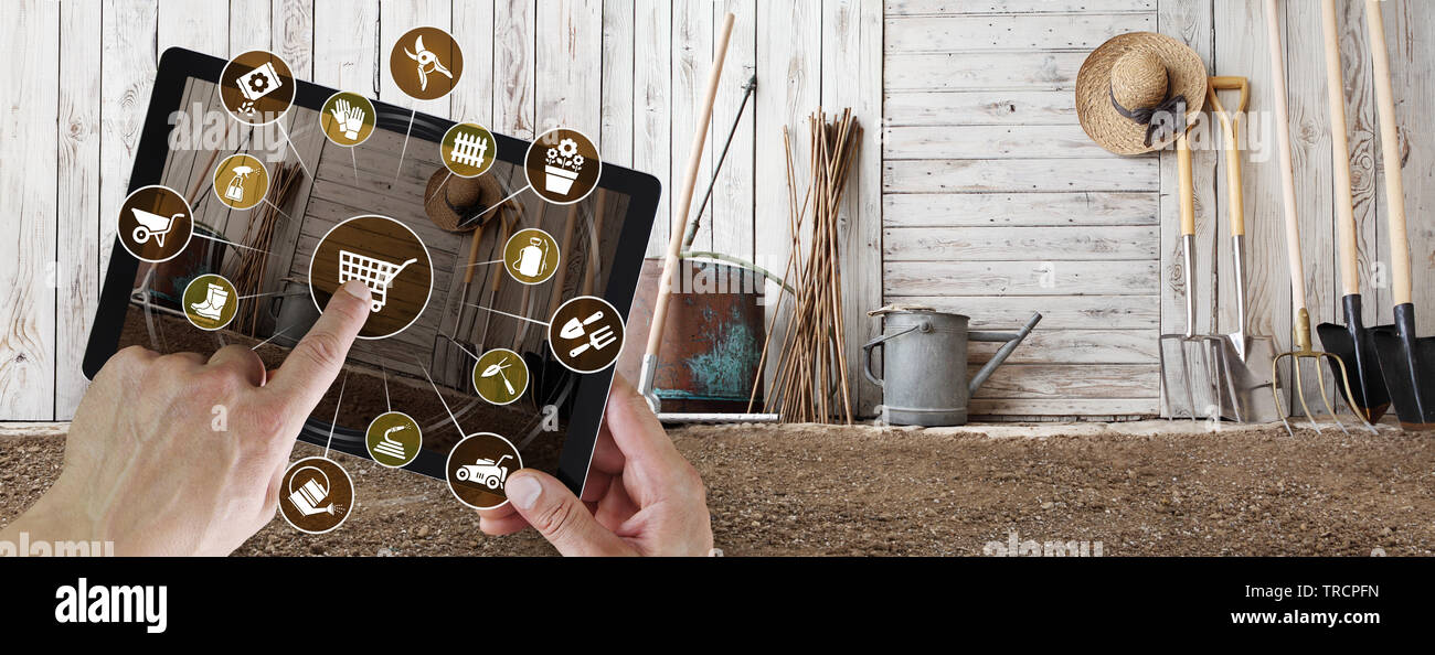 gardening equipment e-commerce concept, online shopping on digital tablet, hand pointing and touch screen with garden tools icons, tool shed in the ba Stock Photo