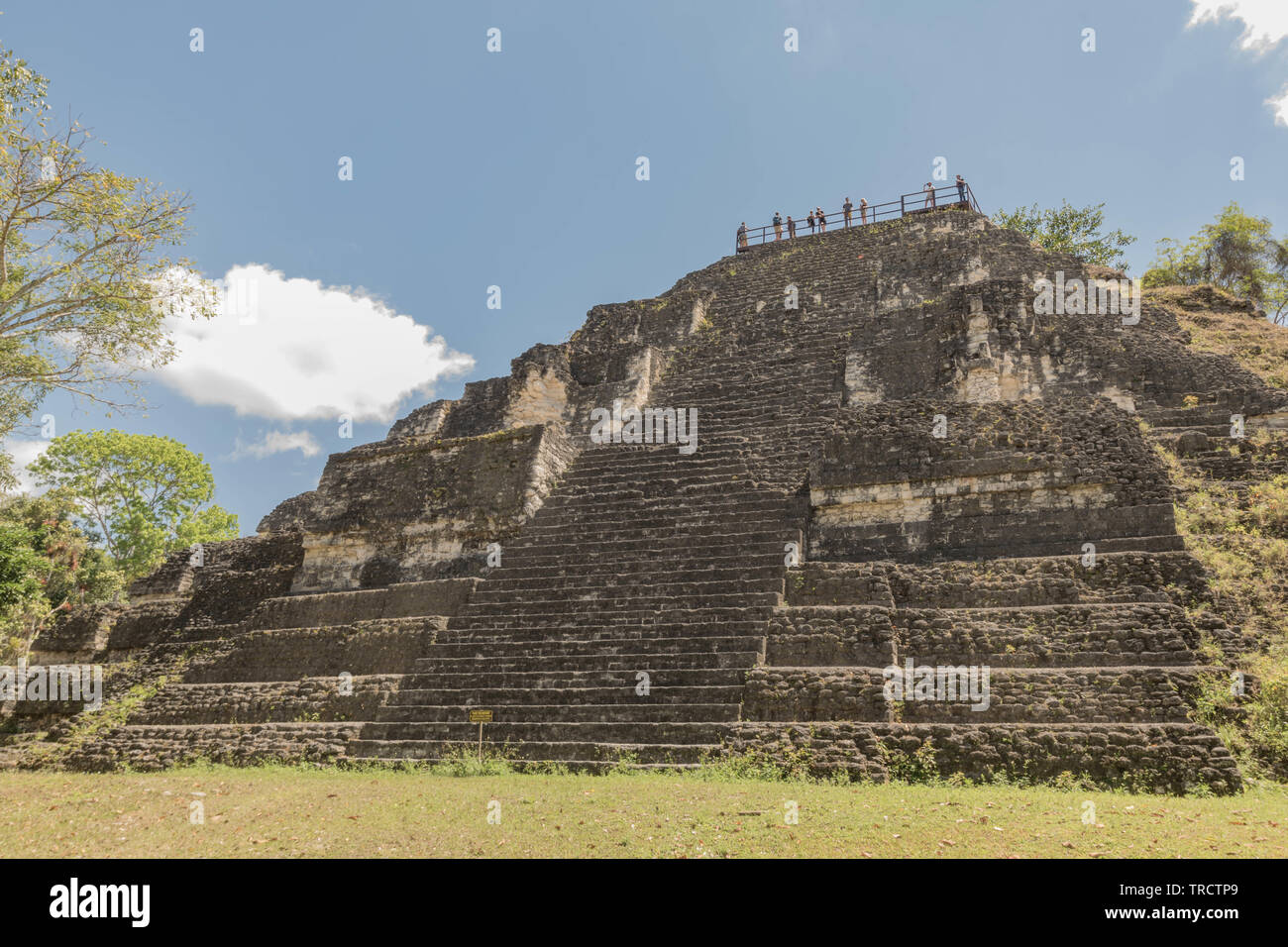 Ancient Mayan Pyramid with people standing at the top, in Tikal National Park, Guatemala - Stock Image