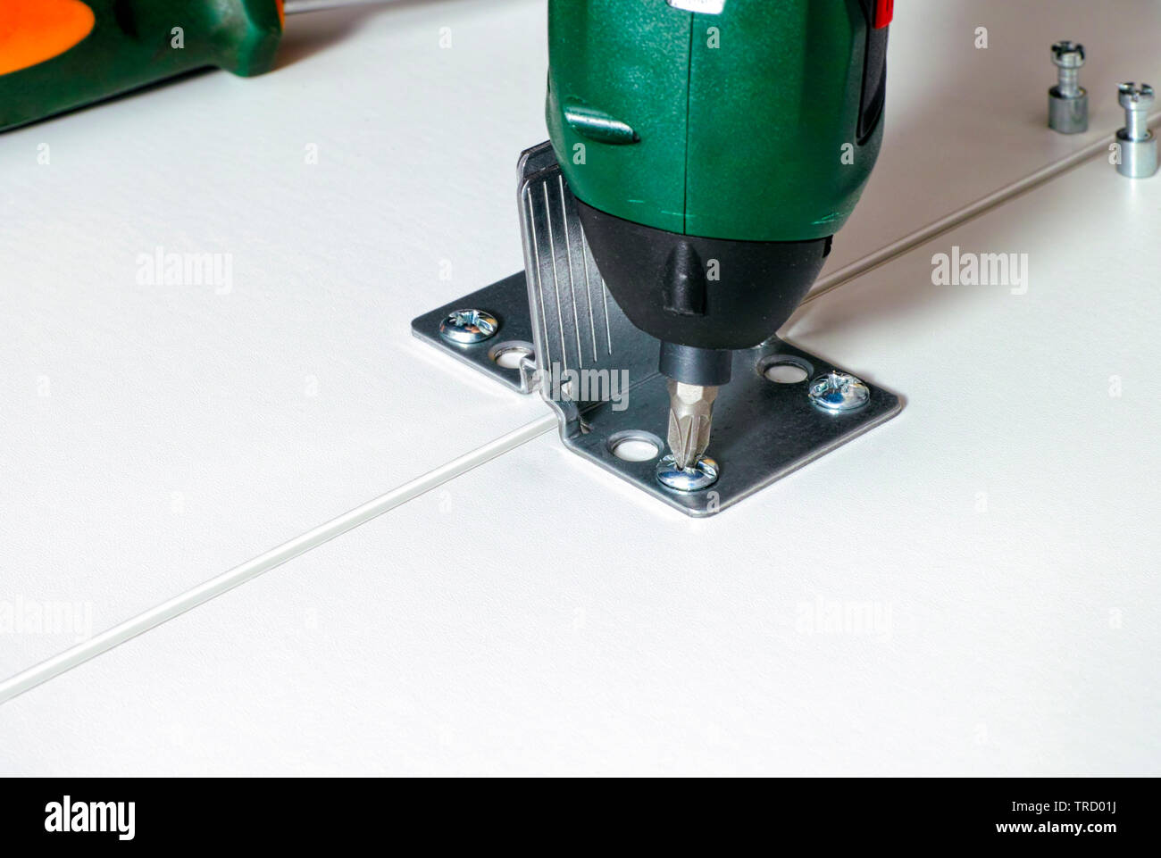 Screw drill twisting the screw on the furniture. Close-up. - Stock Image