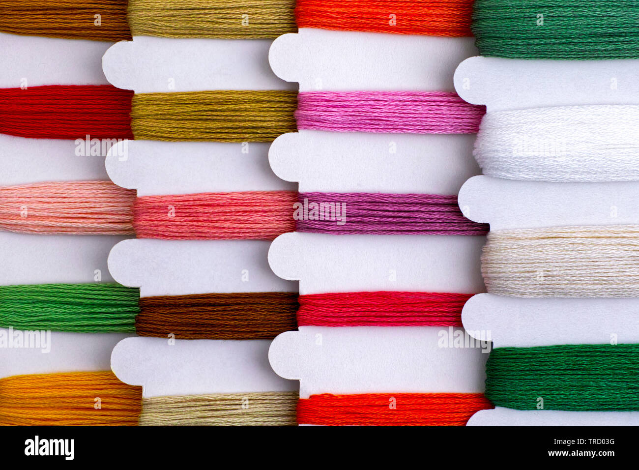 Colored embroidery threads on spools in a row ready for cross stitch. Close-up. - Stock Image