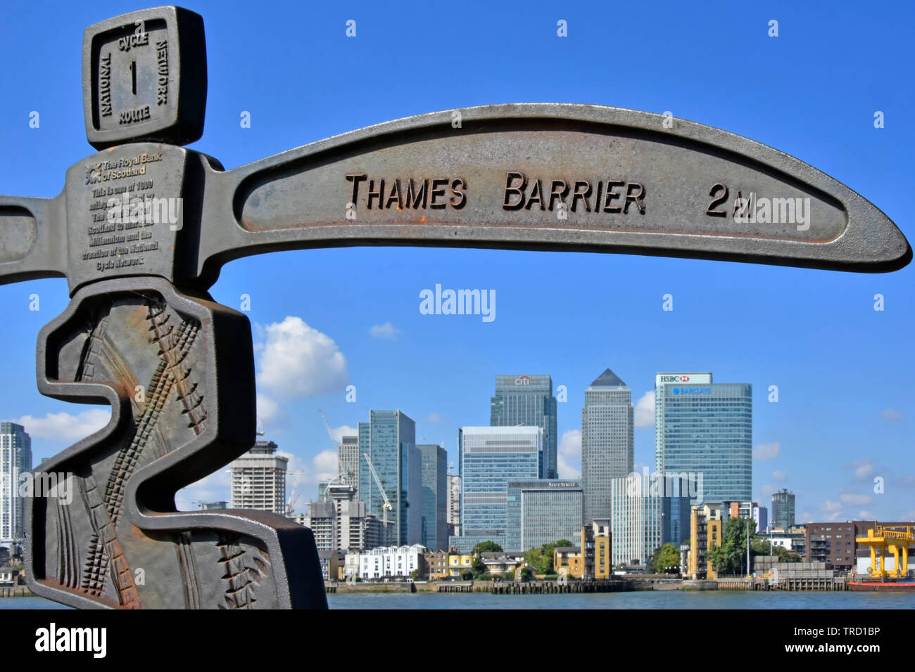 Signpost on riverside towpath to mark the Millennium beside River Thames & forms part of National Cycle network Canary Wharf skyline London England UK Stock Photo