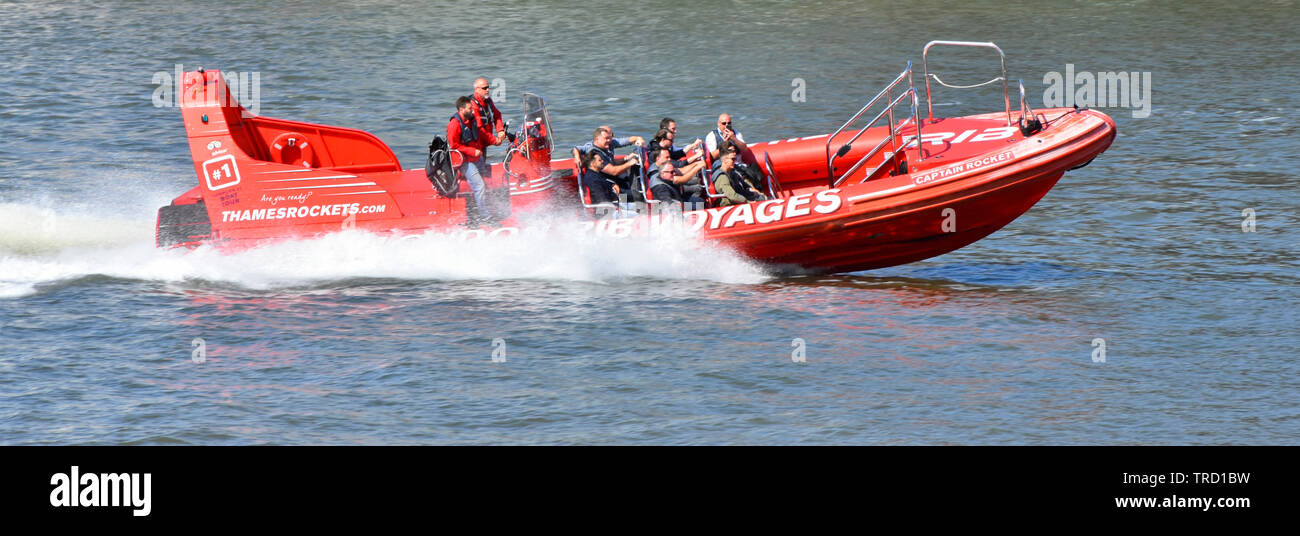 Close up Thames Rockets RIB speedboat ride tourists on fast River Thames sightseeing trip crew at controls of red rib inflatable boat East London UK - Stock Image