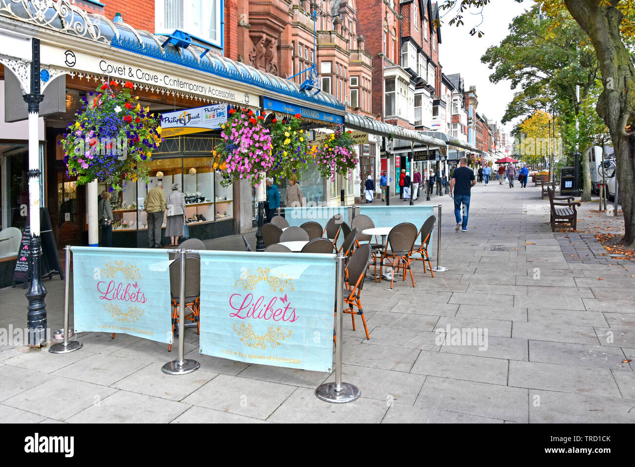 Cafe waits for trade in seaside town shopping street scene old glass canopies & colourful hanging baskets over shop front Lord Street Southport UK Stock Photo