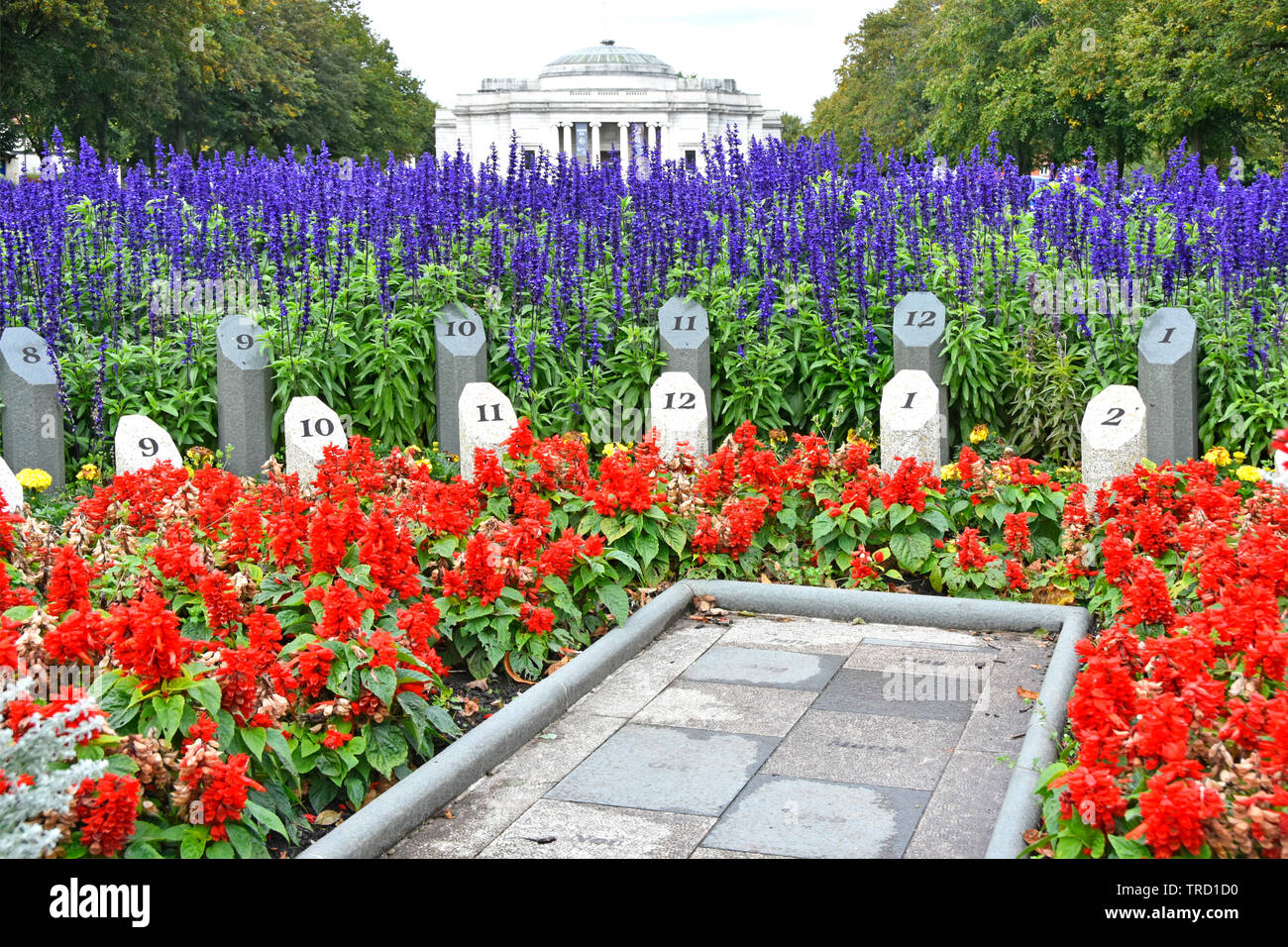 Port Sunlight village Diamond garden view of red salvia & blue delphinium flowers planted around an  Analemmatic sundial Wirral Cheshire England UK - Stock Image