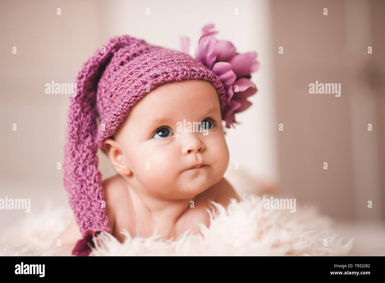 outlet los angeles buying now Funny baby girl wearing knitted hat lying in bed closeup ...