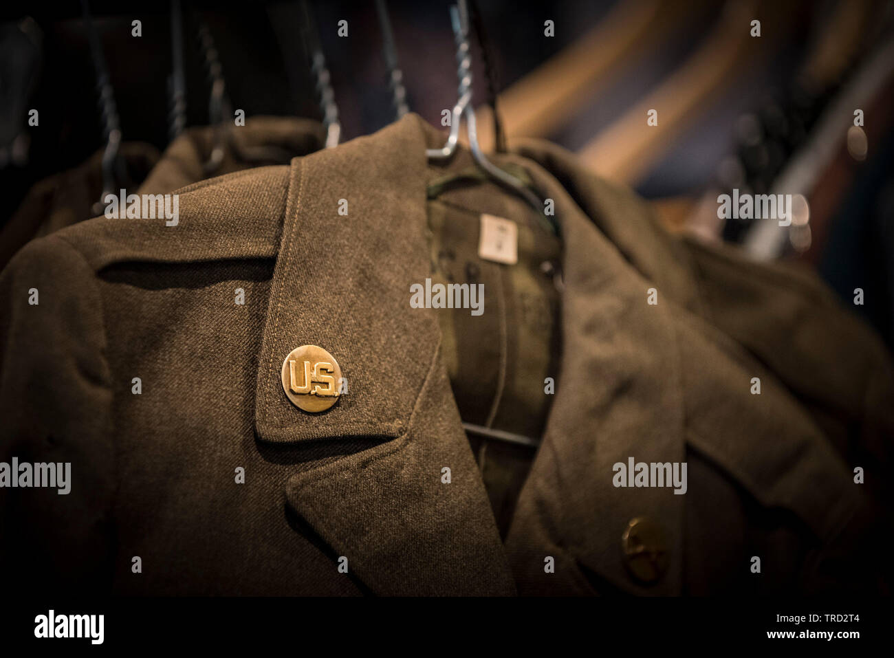 A close up view of the brass 'Enlisted Man' emblem on the uniform tunic of a World War II American Infantryman. - Stock Image