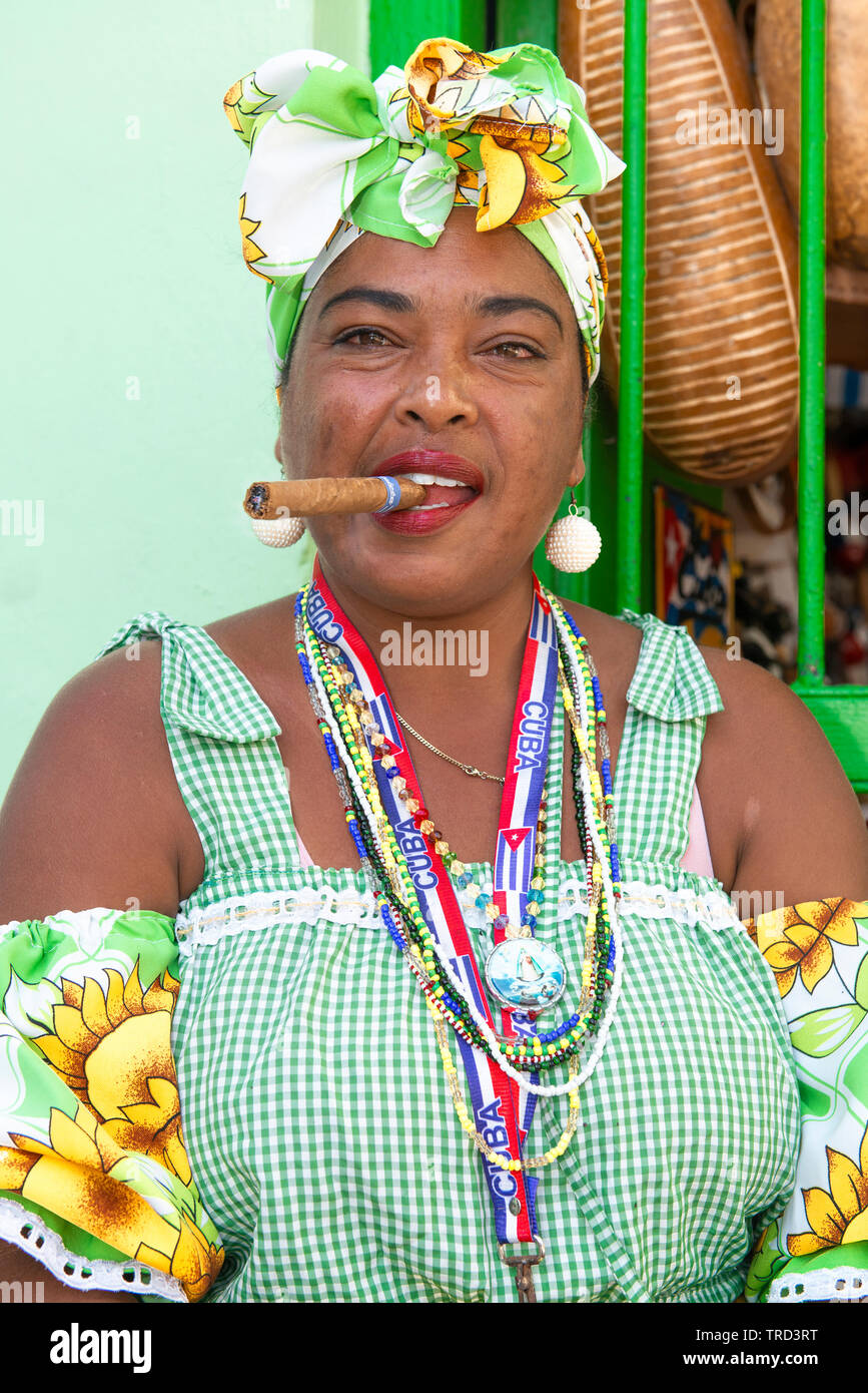 Colourfully dressed cuban lady sitting smoking a large cigar in one of the streets in the Old Town of Havana, Cuba, Caribbean Stock Photo