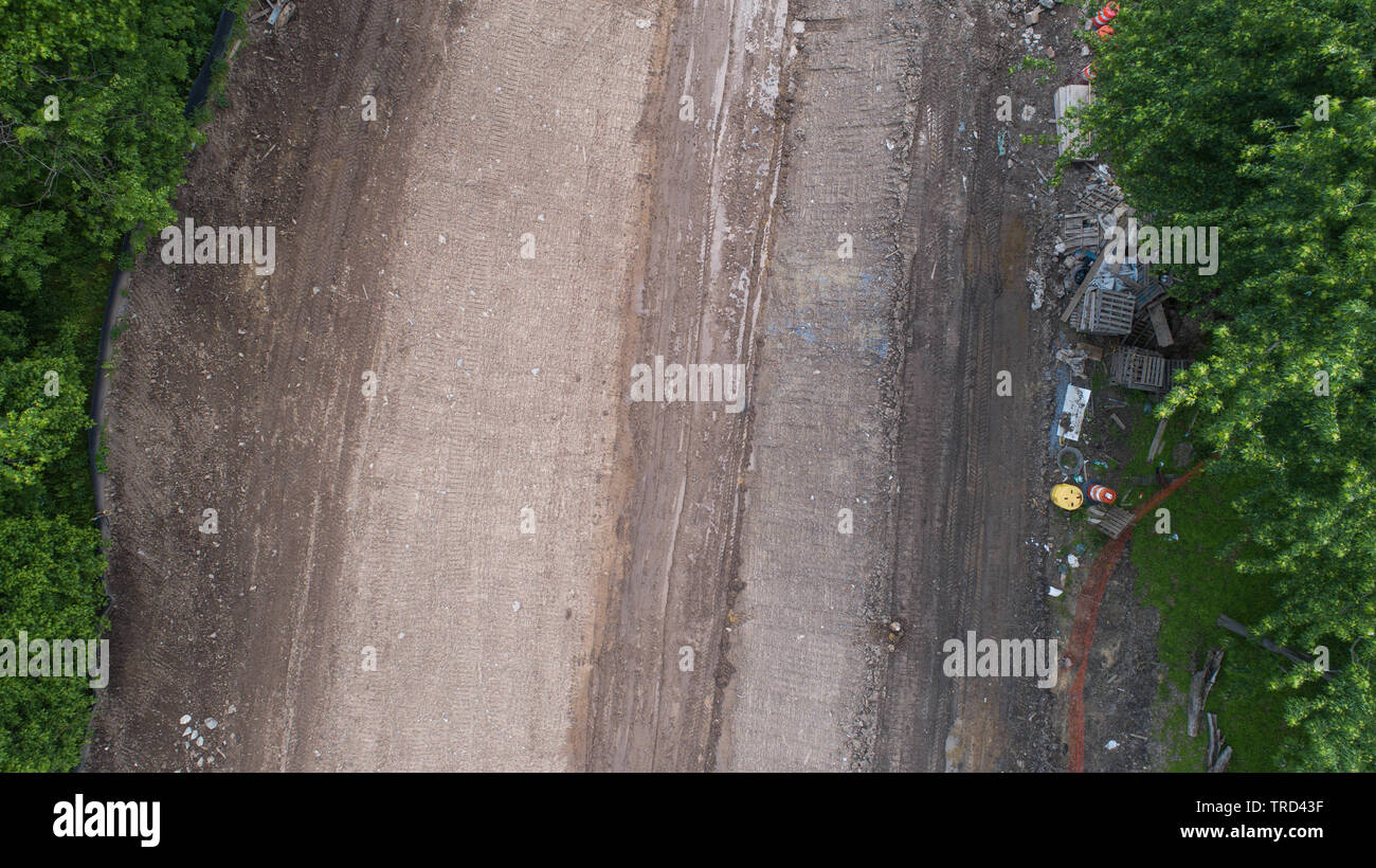 Aerial Drone Photography View Looking Down Directly Over Dirt Road Construction Site with Tire Tracks and Debris Trash Pile Colorful Green Trees - Stock Image