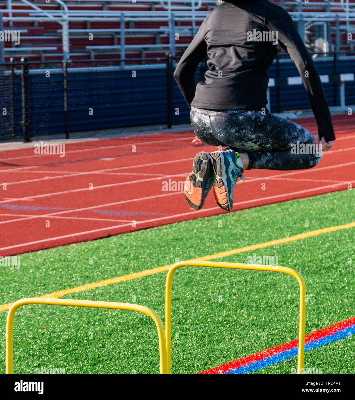 A female track and field sprinter is jumping over two foot yellow hurdles for strength, balance and coordination on a green turf field with the bleach Stock Photo