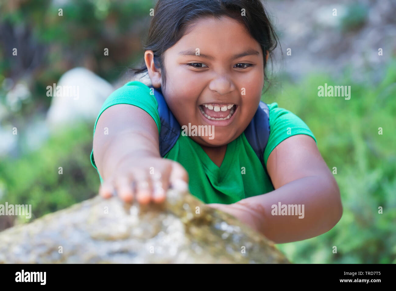 Pre teen student with backpack blocking a water fountain with her hands and having a great time playing after school. - Stock Image