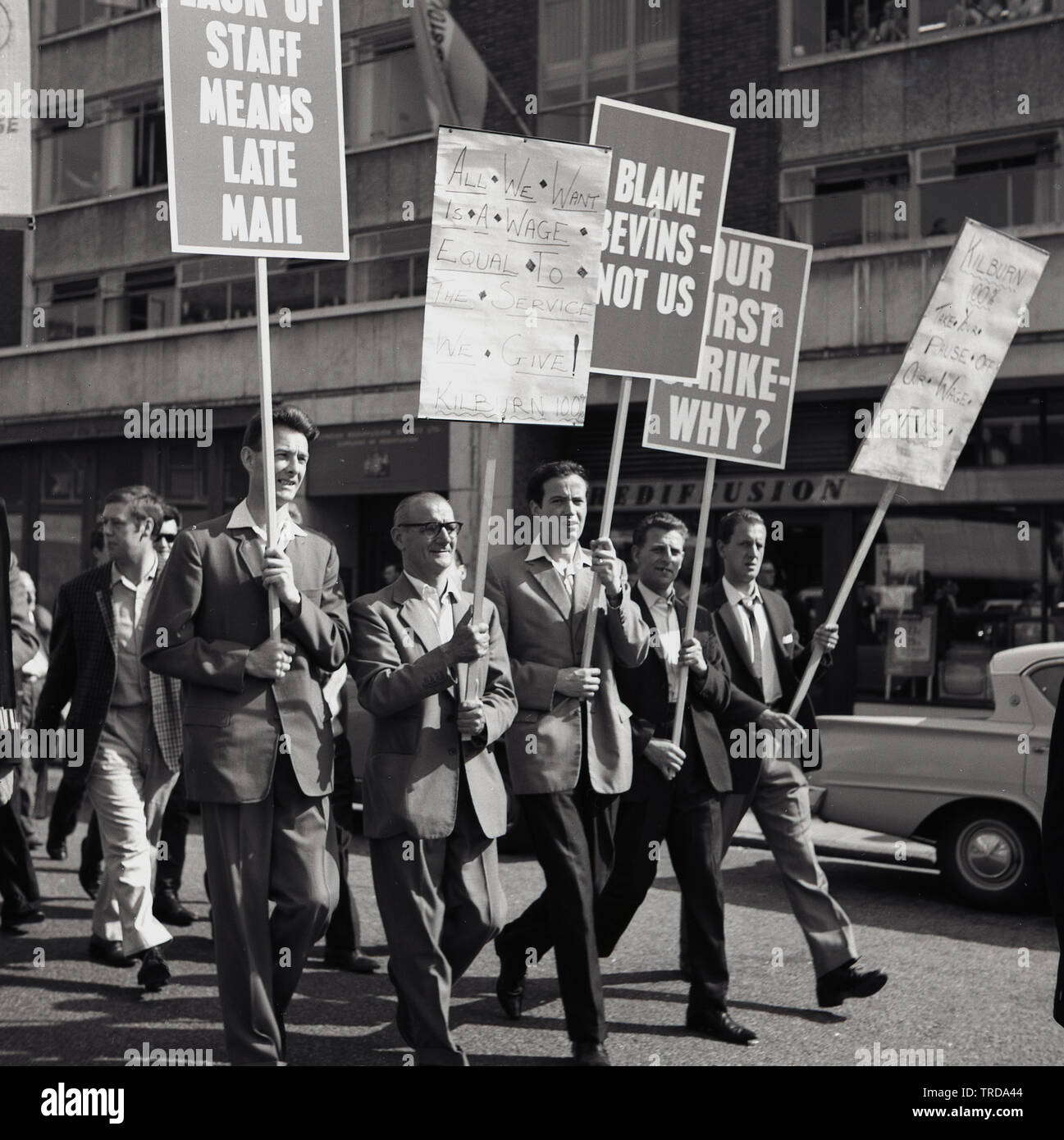 1960s, historical, striking Royal Mail postal workers walking through Central London holding banners, one saying...'Our first strike Why?  The postmenfrom the Kilburn branch were protesting about low wages and blaming the minster Bevin. - Stock Image