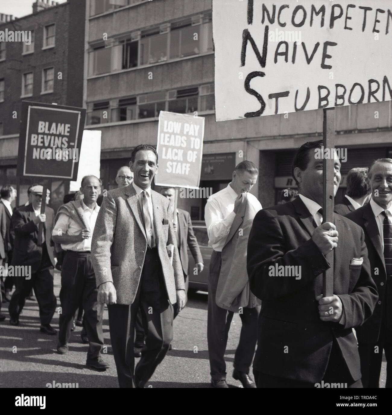 1960s, historical, striking Royal Mail postal workers walking through Central London holding banners, one saying...'Low Pay Leads To Lack of Staff'.  The postmenfrom the Kilburn branch were protesting about low wages and blaming the minster Bevin for the strike taking place, saying he and his minsters were 'Incompetent, Naive  and Stubborn. - Stock Image