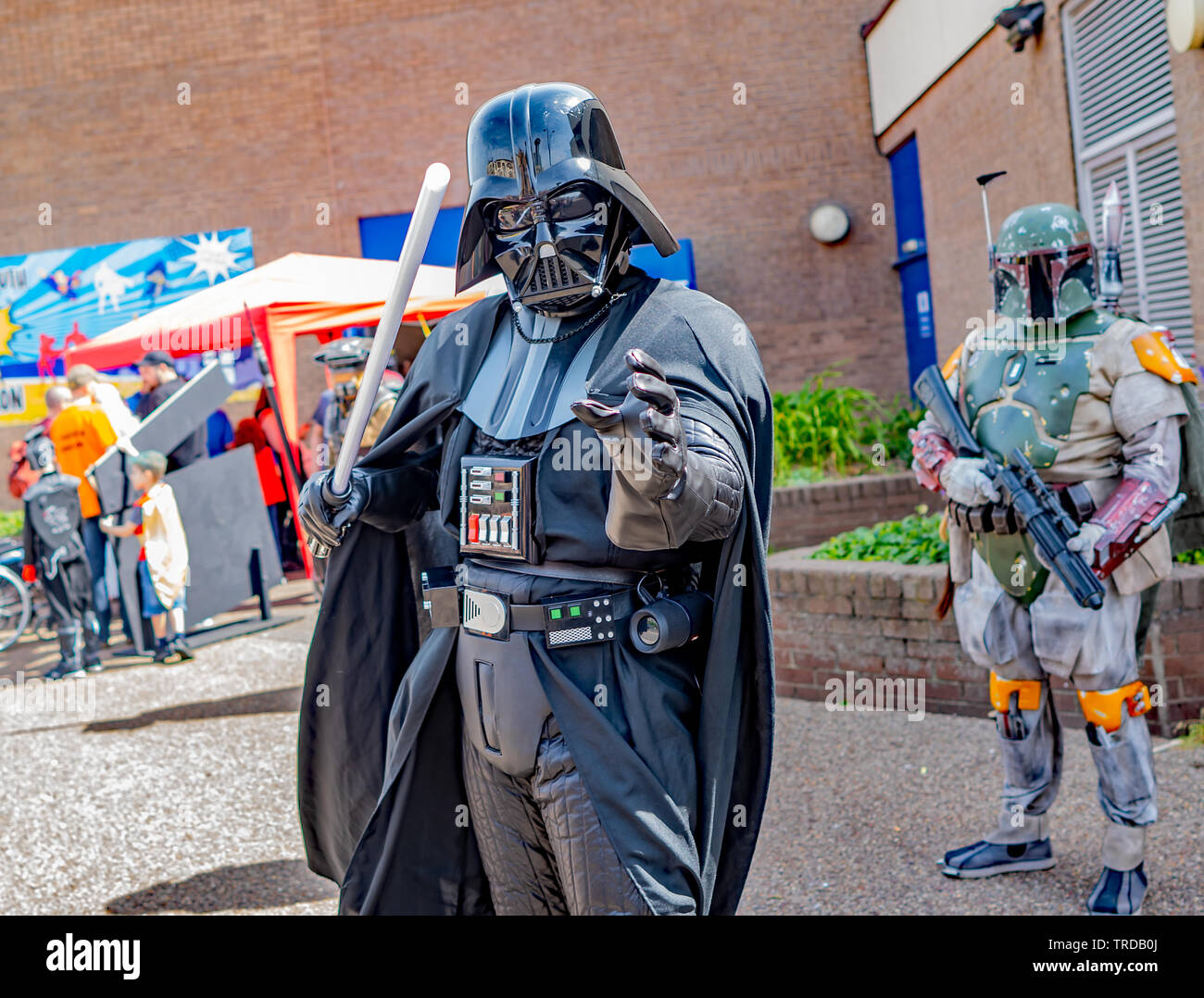 Great Yarmouth Comicon 2019 – A close up portrait of man dressed up as Darth Vader, with a storm trooper in the background, outside the entrance to th - Stock Image