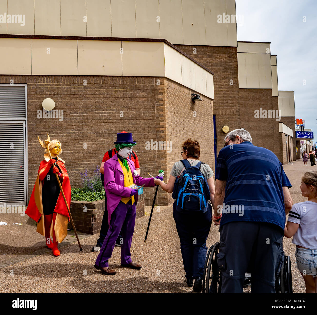 Great Yarmouth Comicon 2019 – The Joker, Mario and a super heroine outside the entrance of the Comicon event in the seaside town of Great Yarmouth - Stock Image