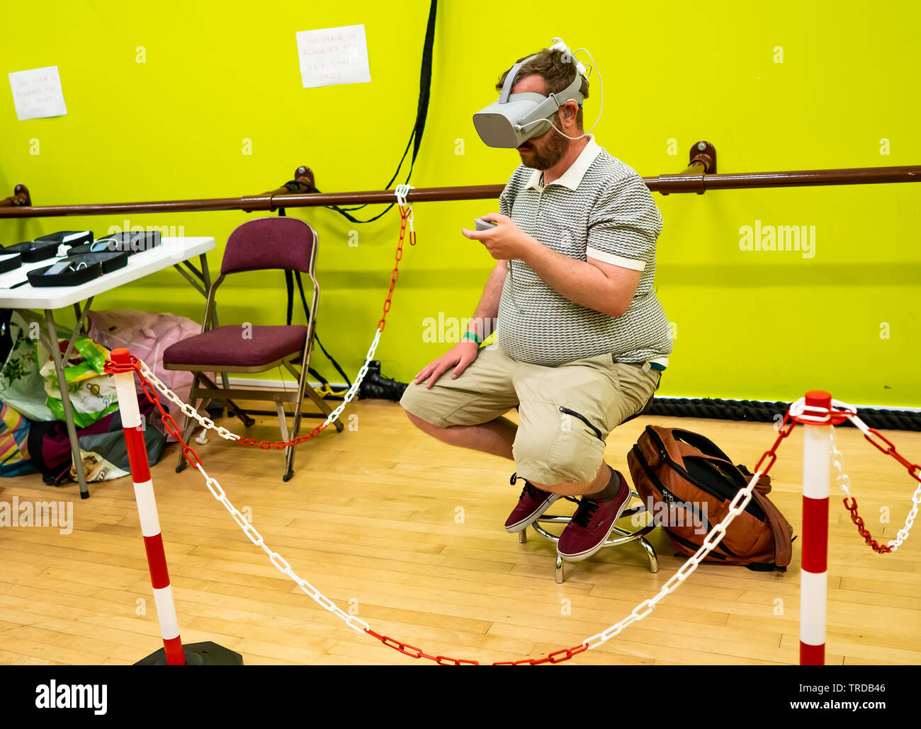 Great Yarmouth Comicon 2019 – Young man sitting on a chair immersed in a virtual reality computer game at the Comicon event in the seaside town of Gre - Stock Image