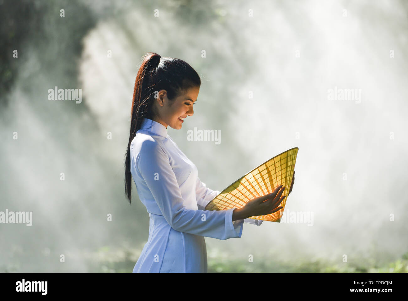 Asia woman vietnam or chinese style dress / Portrait of beautiful young girl vietnamese traditional costume wearing with hat weaving leaf in hand on n - Stock Image