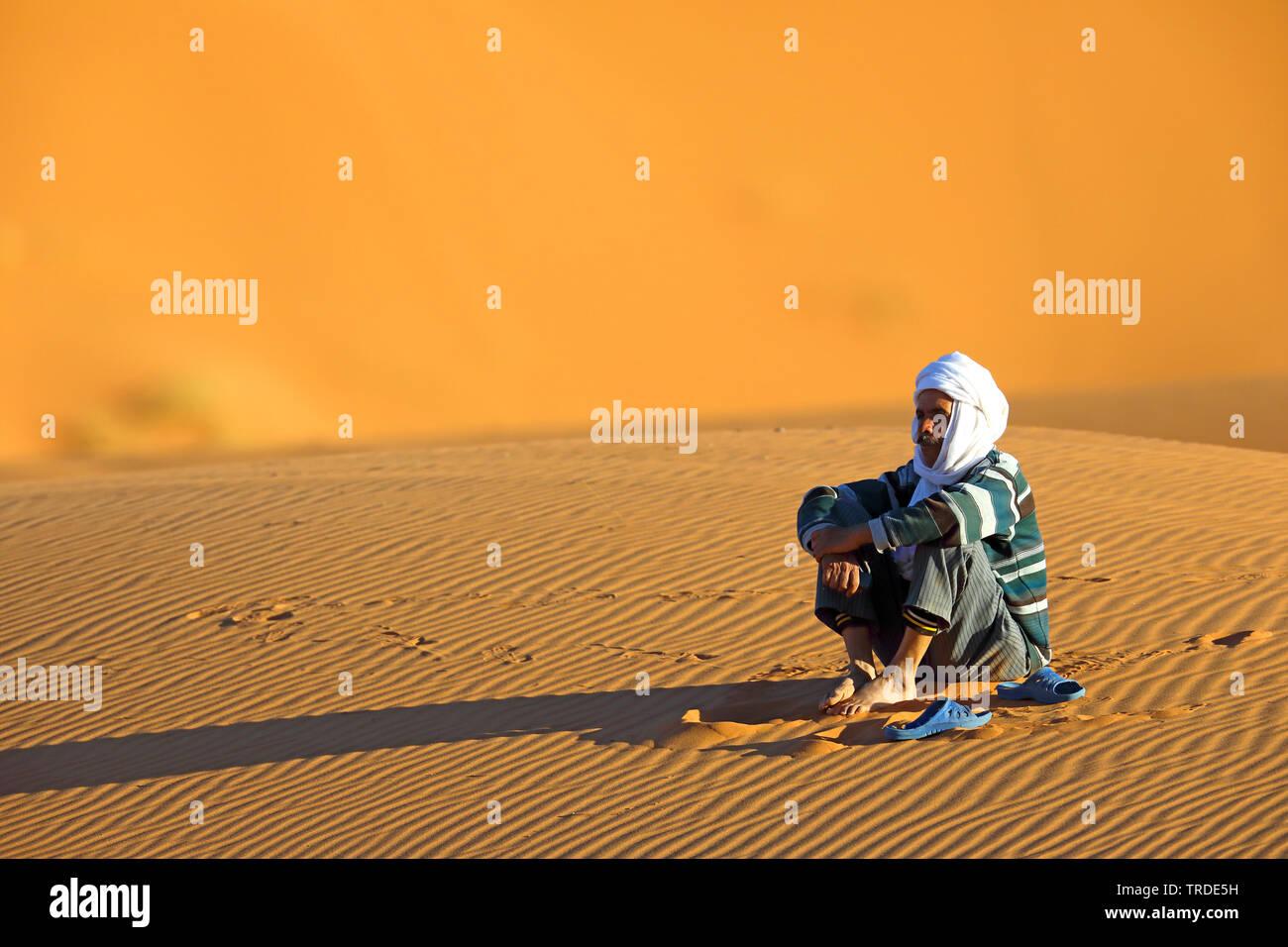 Berber sitzt im Wuestensand, Marokko, Merzouga, Erg Chebbi | Berber sitting in desert sand, Morocco, Merzouga, Erg Chebbi | BLWS501582.jpg [ (c) blick - Stock Image
