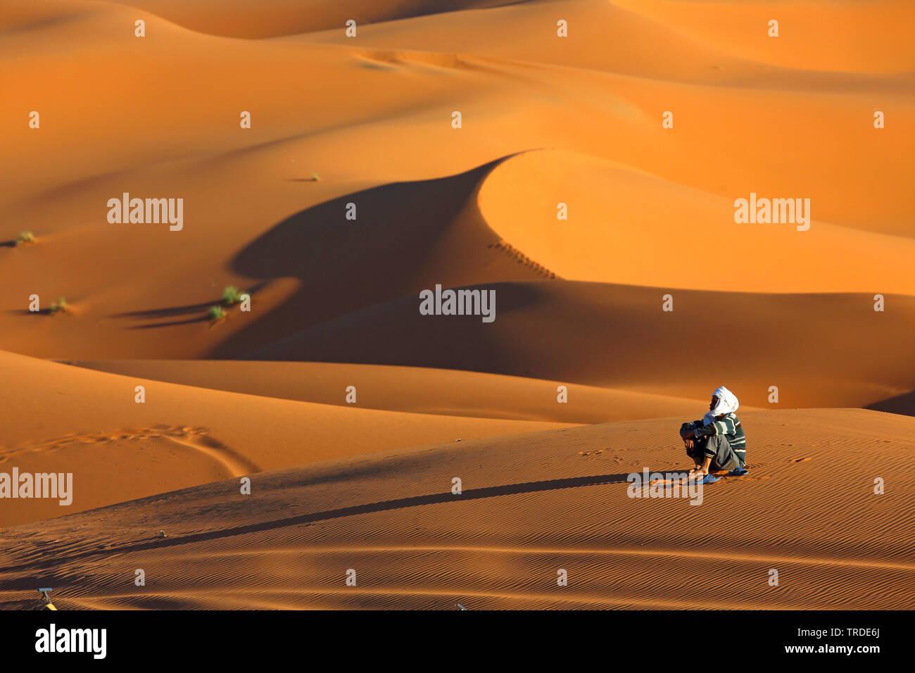 Berber sitzt im Wuestensand, Marokko, Merzouga, Erg Chebbi | Berber sitting in desert sand, Morocco, Merzouga, Erg Chebbi | BLWS501606.jpg [ (c) blick - Stock Image