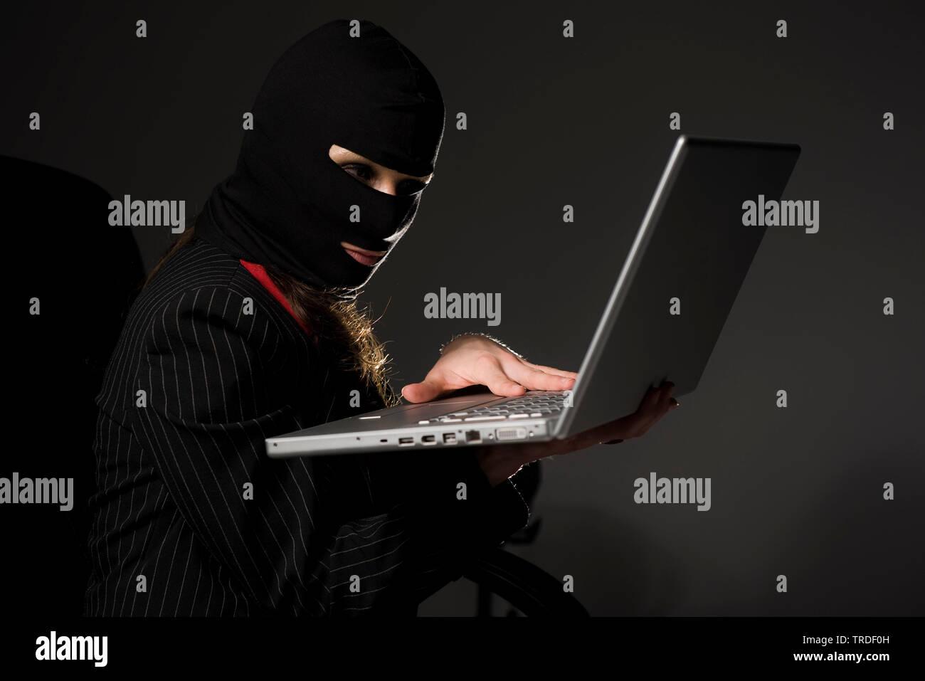 Portraet einer attraktiven Geschaeftsfrau, mit Skimaske auf einem Laptop arbeitend / Internetkriminalitaet | Portrait of an attractive Business woman - Stock Image