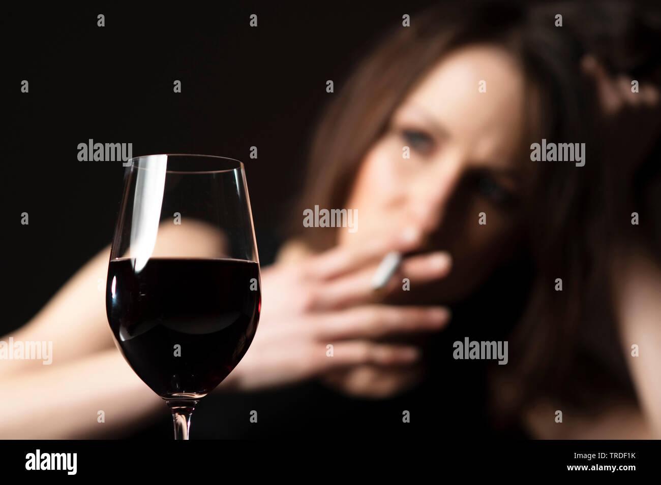 Portraet einer deprimierten und alkoholisierten Frau mit Weinglas, eine Zigarette rauchend | Portrait of a depressed and alcoholised woman smoking a c - Stock Image