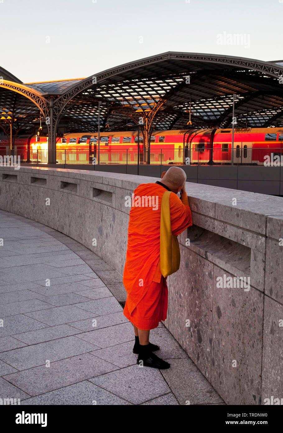 buddhistischer Moench fotografiert den Koelner Hauptbahnhof im letzten Abendlicht, Deutschland, Nordrhein-Westfalen, Rheinland, Koeln   buddhistic mon - Stock Image