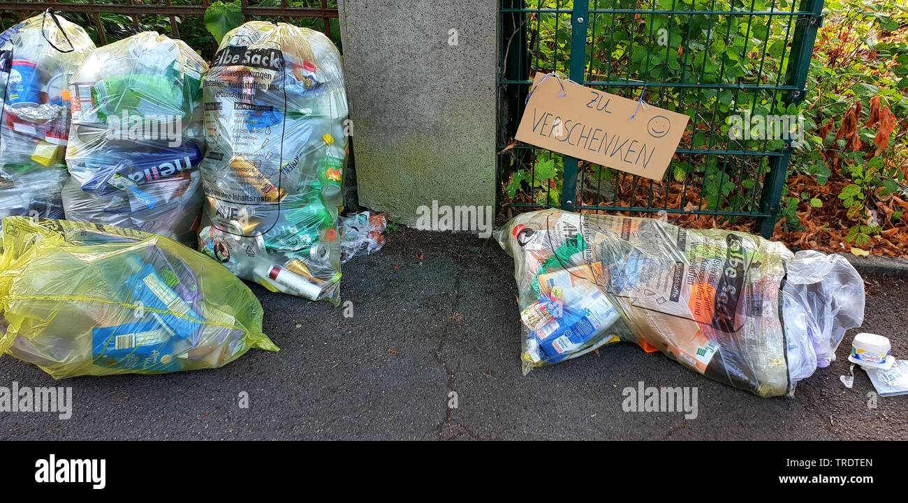 yellow sacs and sign 'giveaway' at a fence, Germany - Stock Image