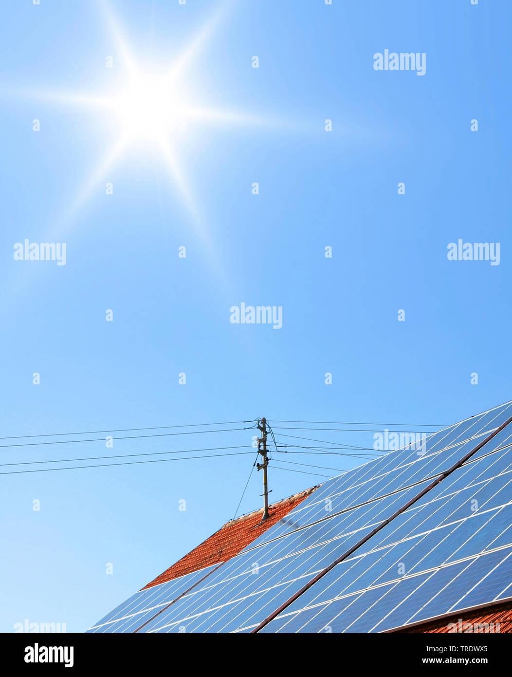 Detailaufnahme eines Hausdachs mit Solarzellen vor wolkenlosem Himmel | Detail of residental house roof with solar panels against cloudless sky | BLWS - Stock Image