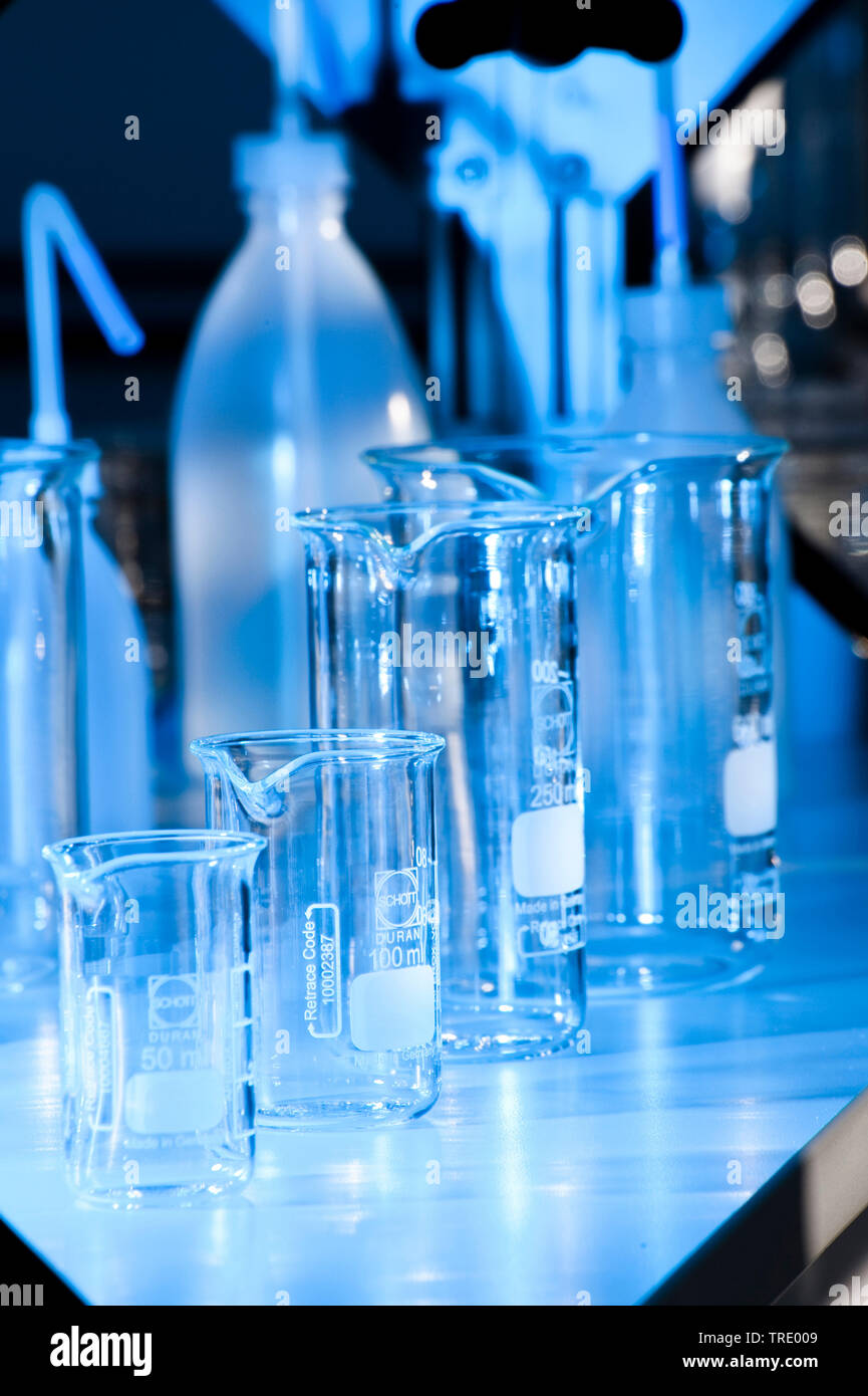 Serveral different flasks and beaker glasses on a laboratory bench illuminated in blue light Stock Photo