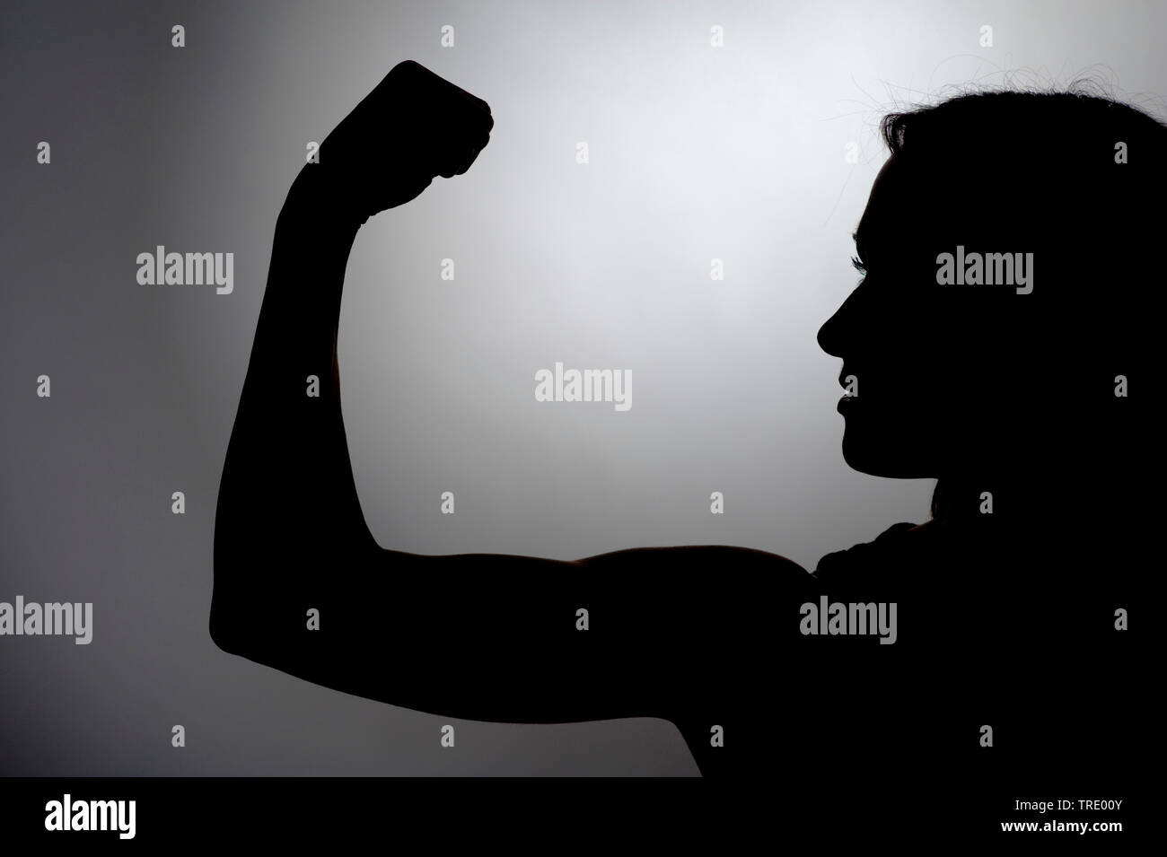 Schwarz-Weiss-Silhouette einer Frau mit angespanntem Bizeps | Black&White silhouette of a woman with toned bicepts | BLWS512919.jpg [ (c) blickwinkel/ - Stock Image