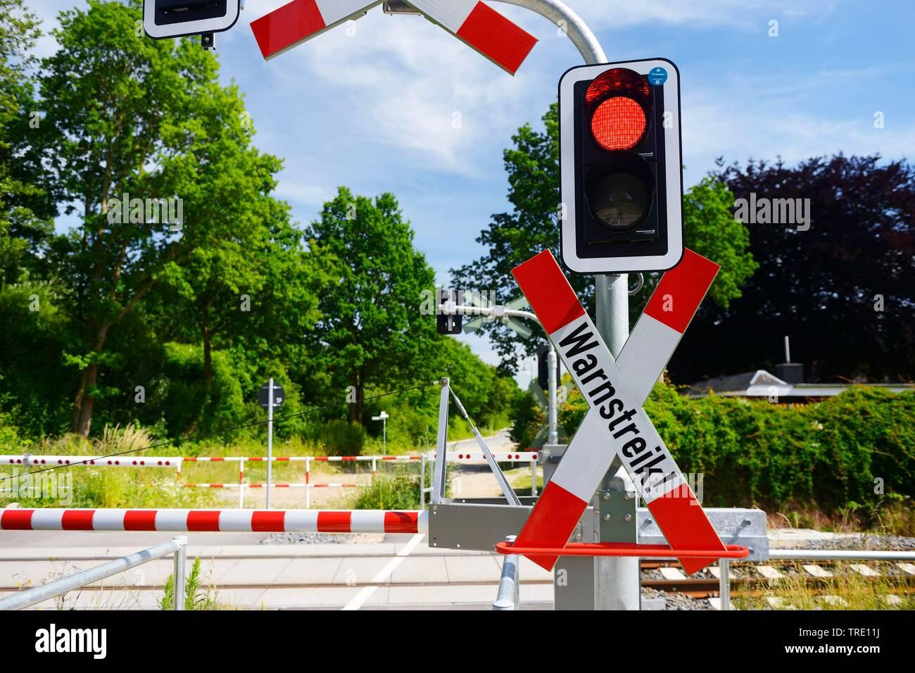 Geschlossener Bahnuebergang mit Aufschrift WARNSTREIK symbolisch fuer Bahnstreik, Deutschland | Closed railway crossing lettering WARNSTREIK (warning - Stock Image